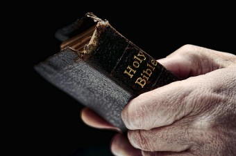 man-hands-holding-old-bible-olivier-le-queinec-340x226[1]